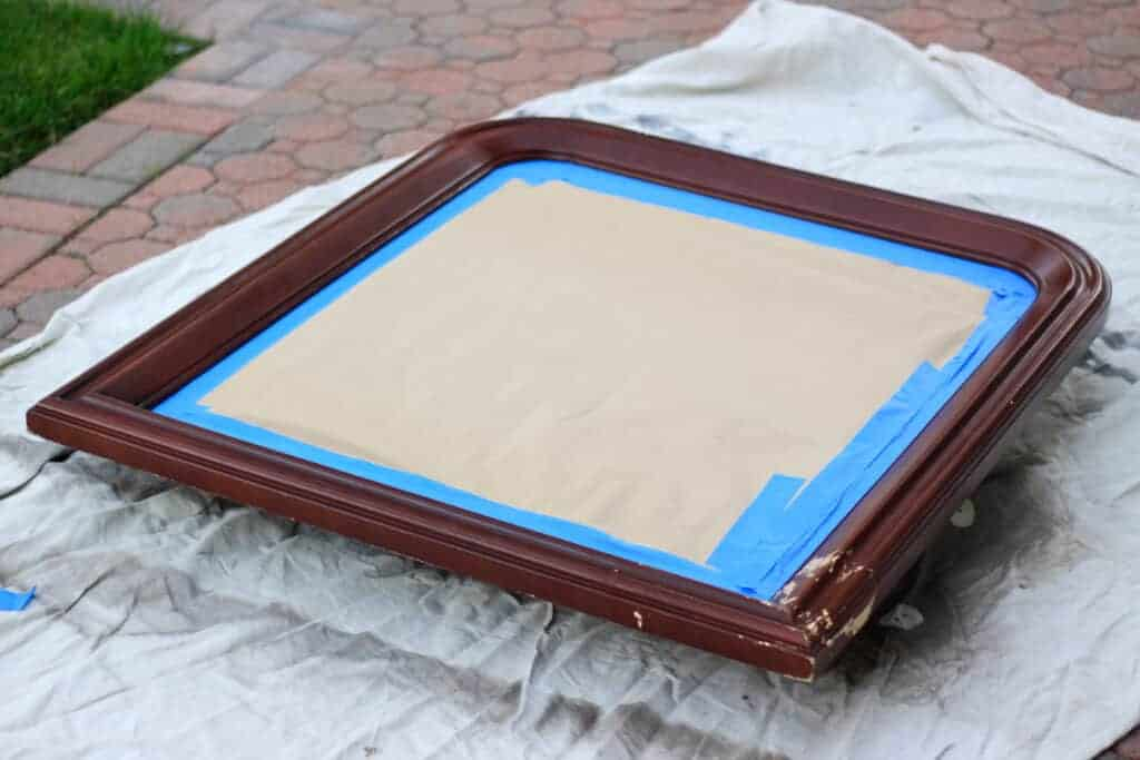 brown framed mirror with tape