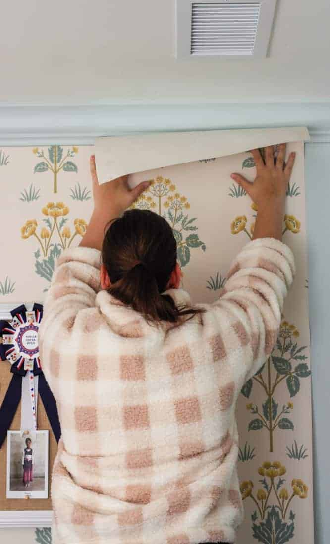 girl pasting wallpaper on the wall