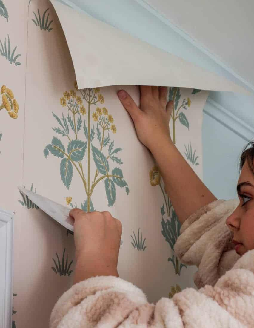 girl smoothing out wallpaper