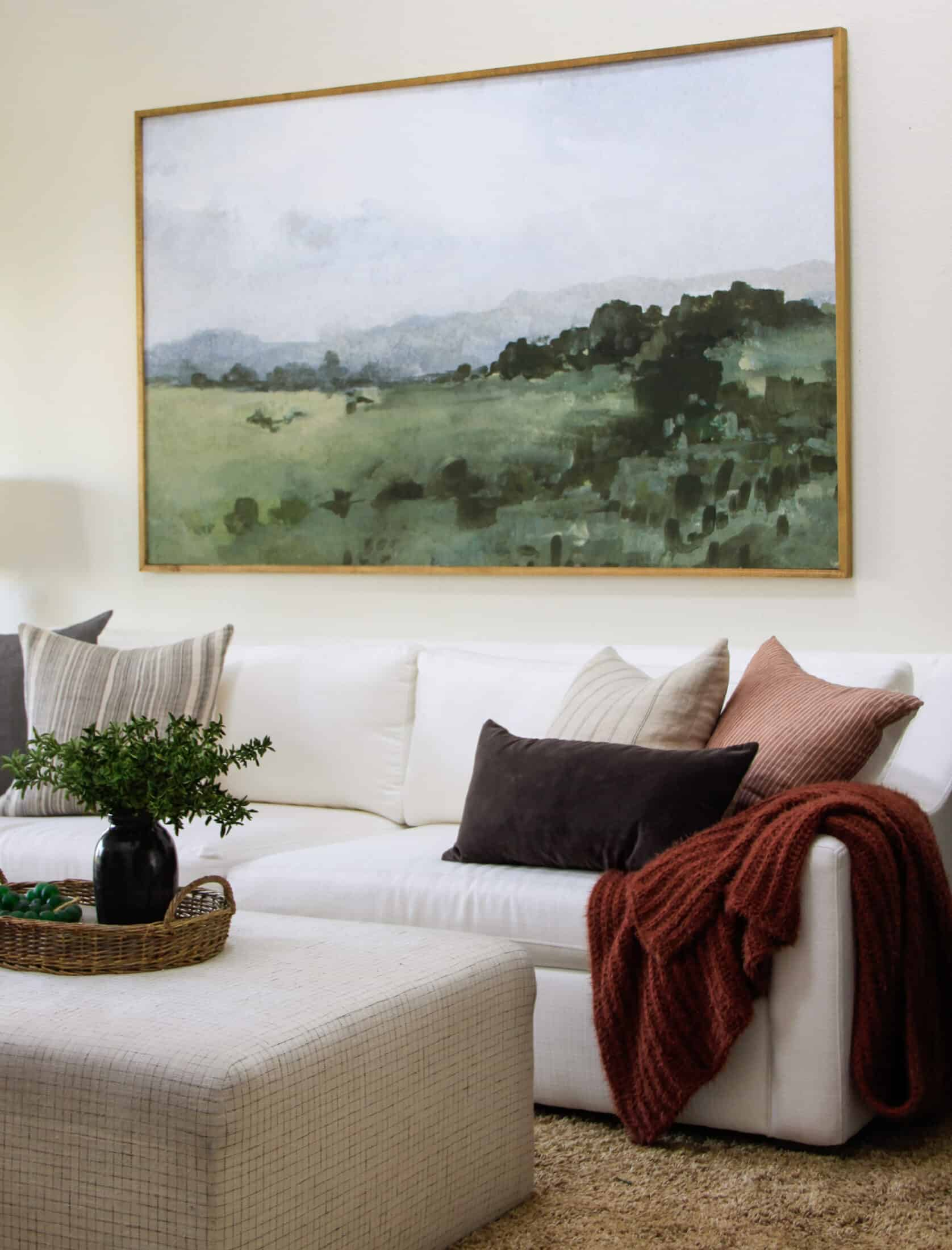 white couch with ottoman, pillows, and framed art above