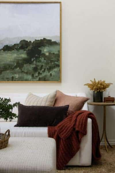 white sofa with neutral pillows and framed artwork above