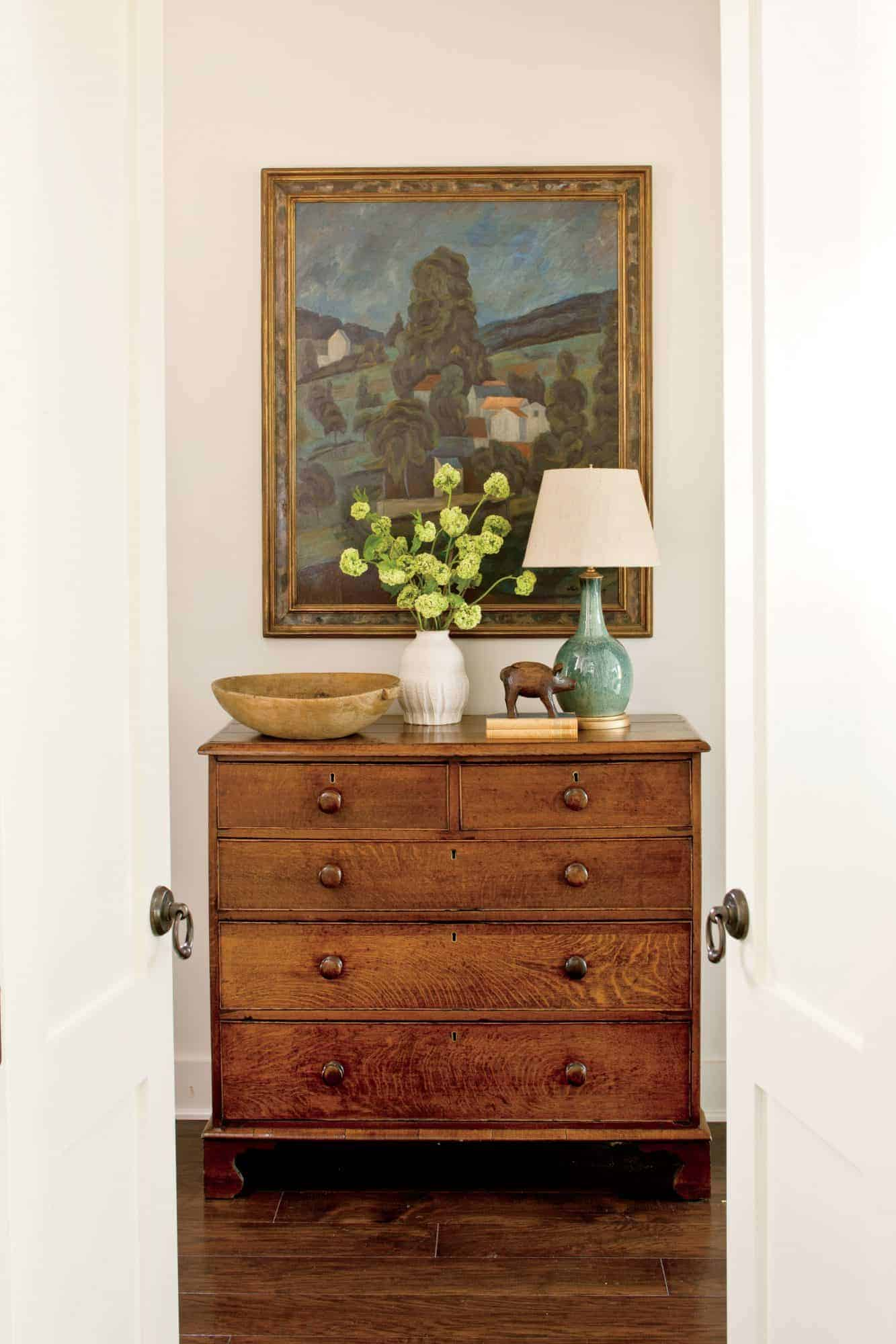 antique dresser with lamp and art above