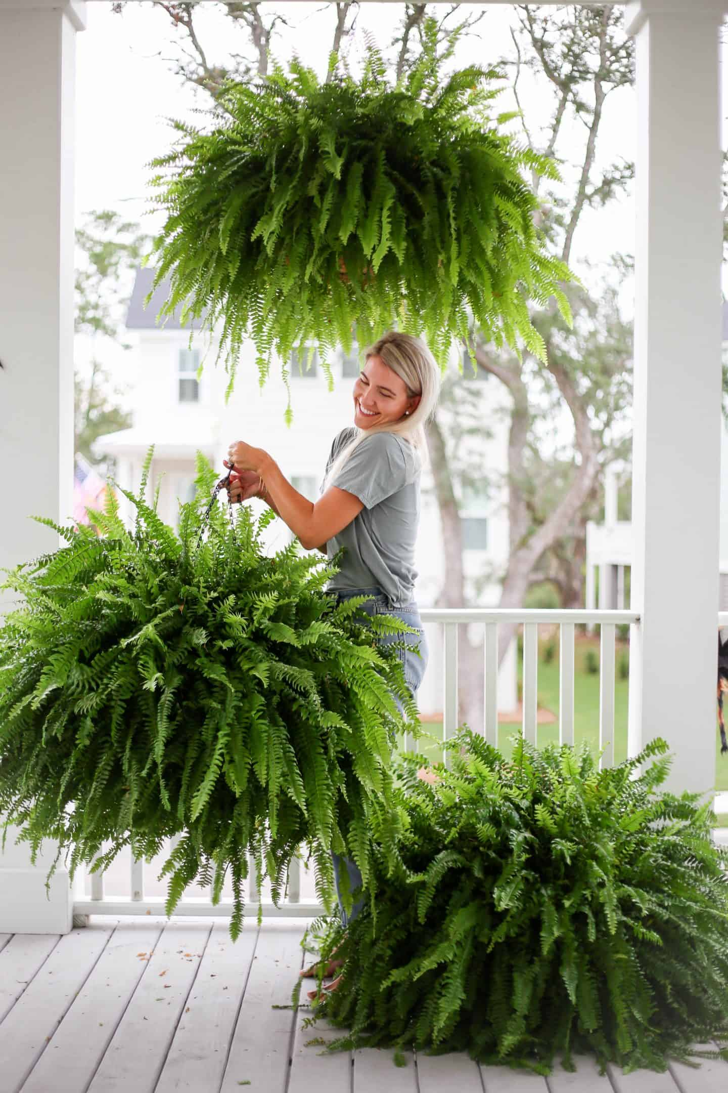 woman holding healthy ferns on a porch