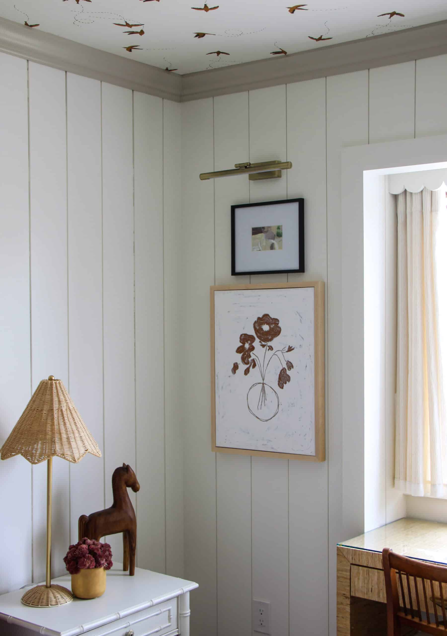 corner of bedroom with vertical shiplap and artwork