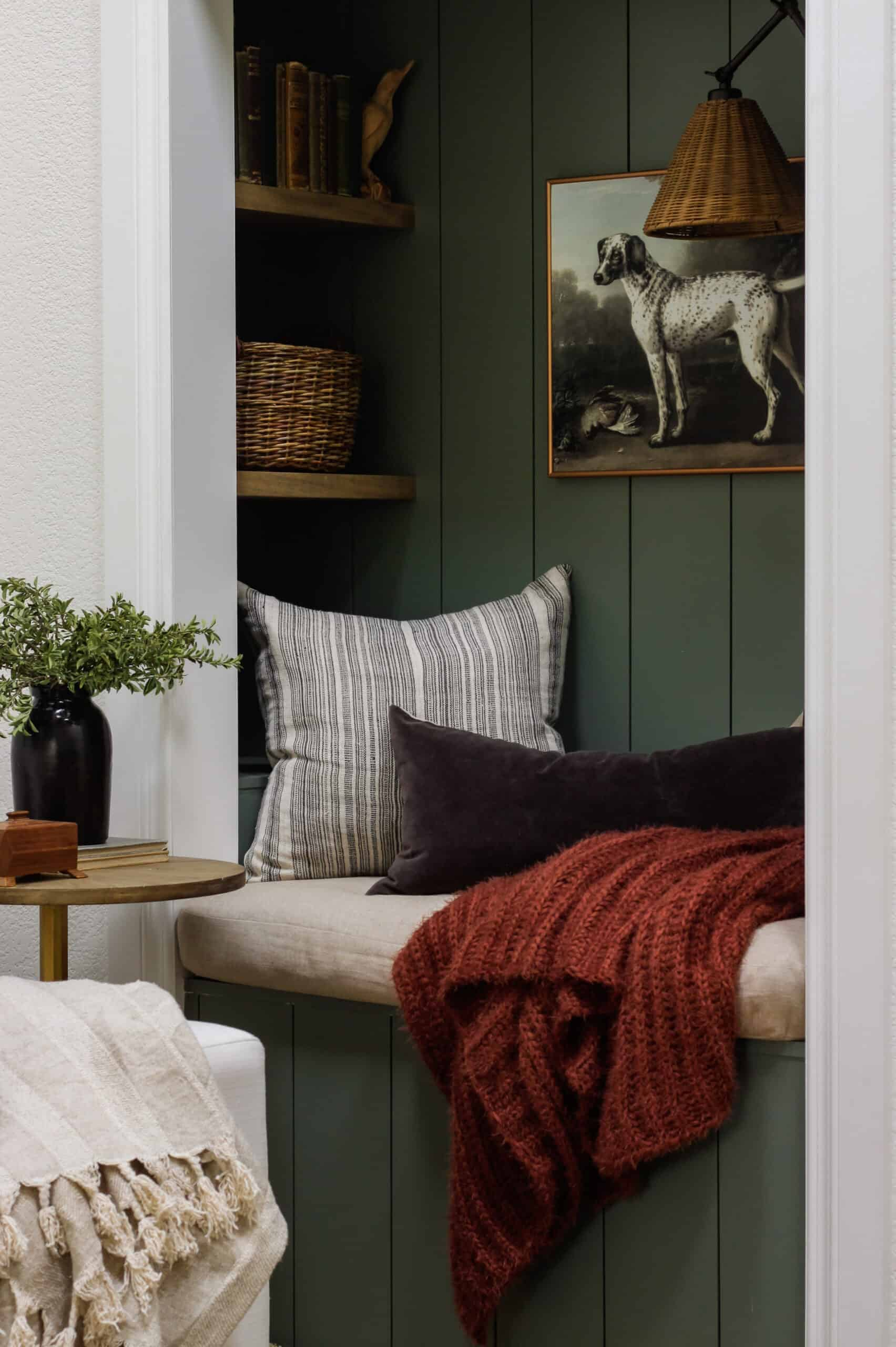 reading nook with green vertical shiplap and rust throw blanket