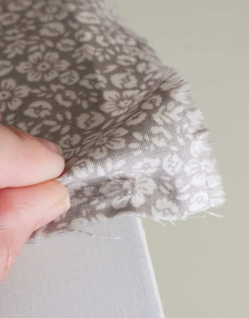 Fingers pleating fabric on a lampshade