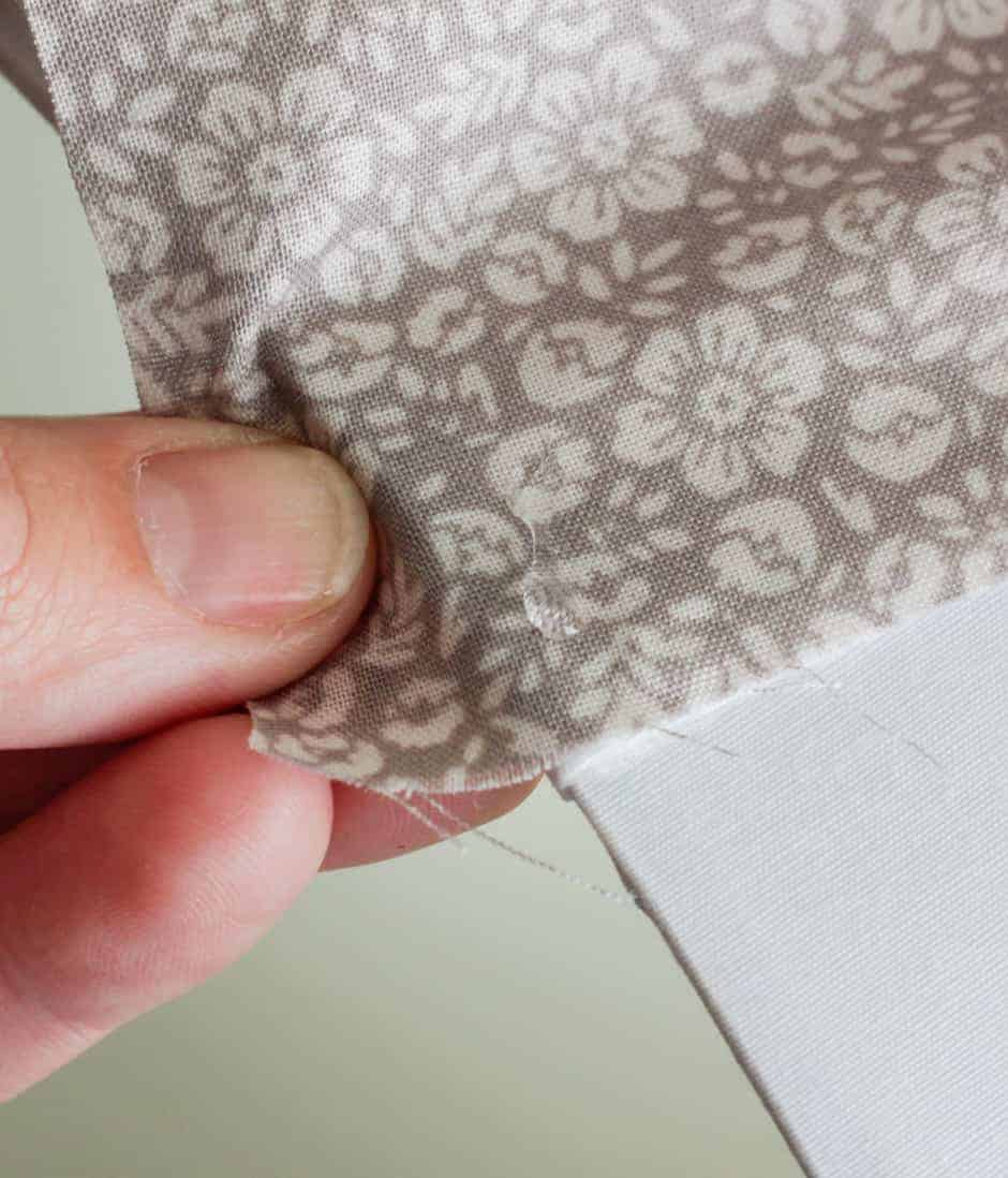 Fingers pulling fabric taut on a lampshade