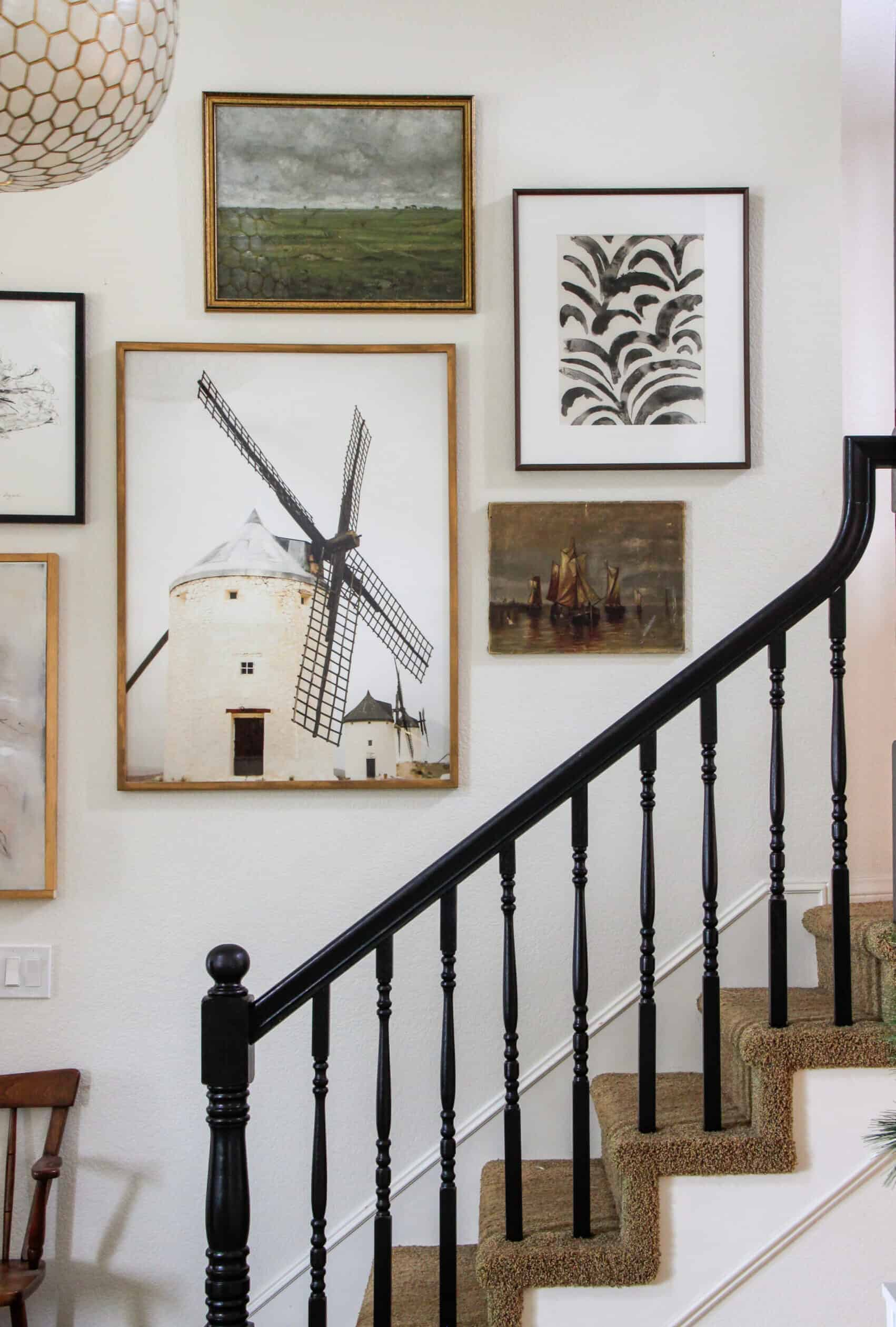 black staircase railing with collected gallery wall