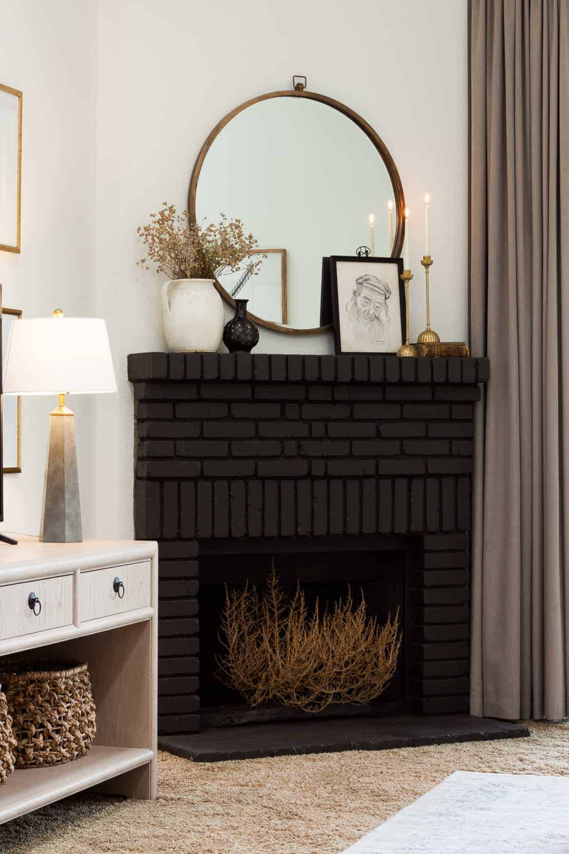Black brick corner fireplace with tumbleweed in opening.