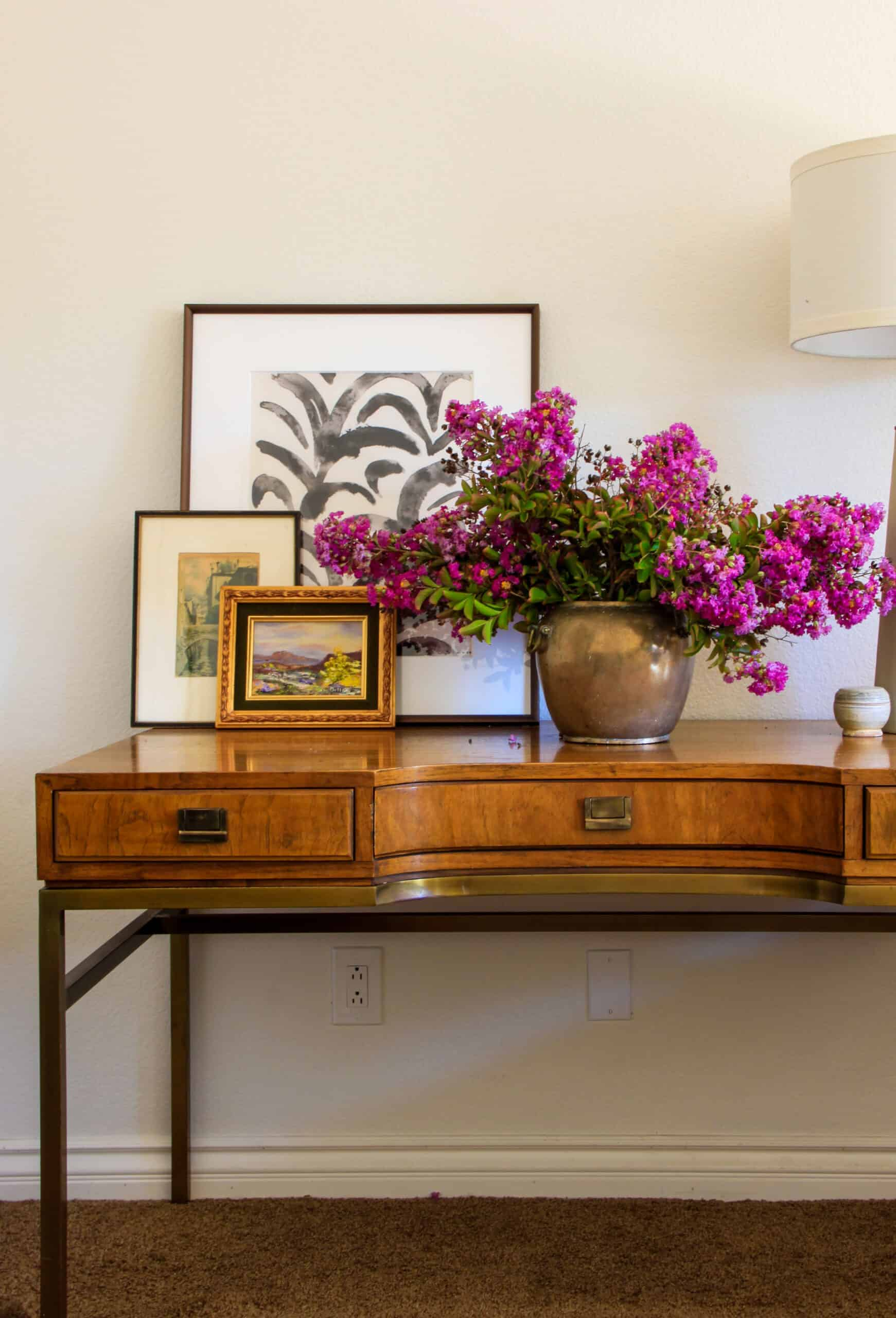 Wooden and brass desk with flowers and art on top