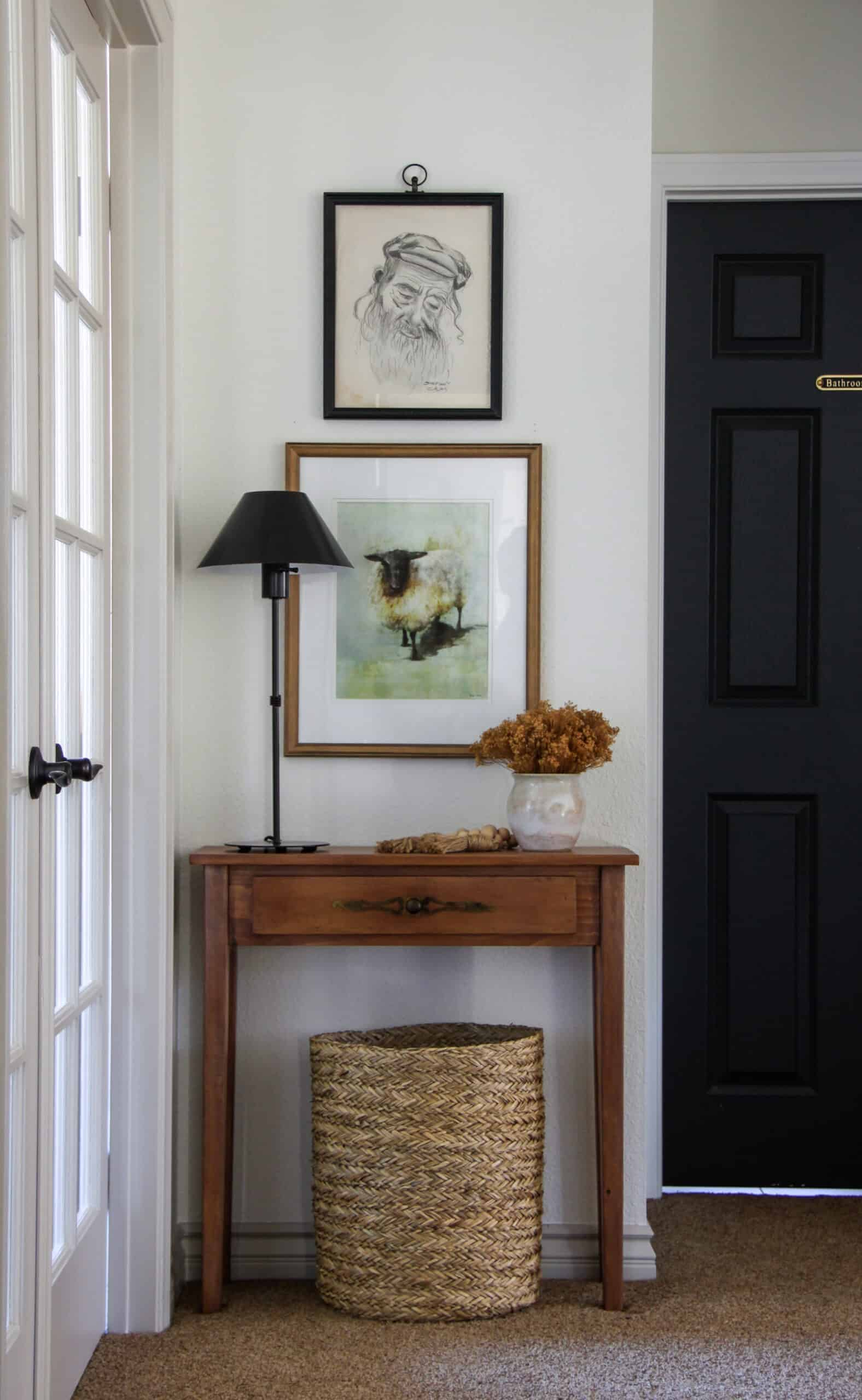 Small hallway table with black lamp and two pieces of art above.