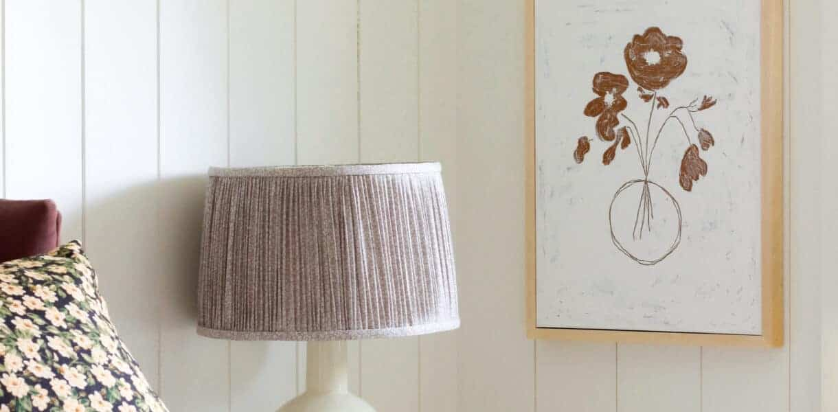 corner of girl's bedroom with artwork and pleated fabric lamp shade