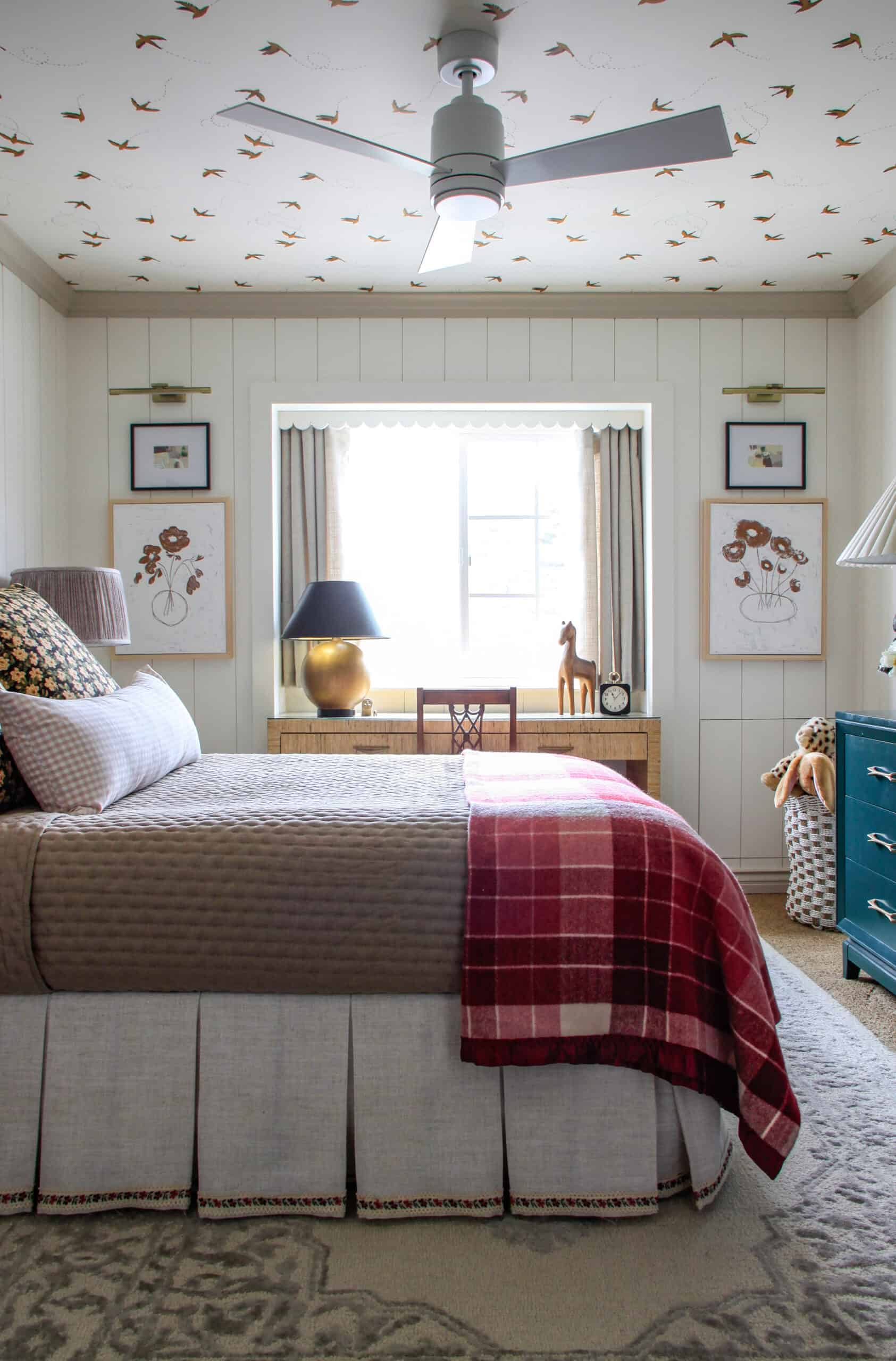 side view of bedroom with pink plaid blanket and bird wallpaper on the ceiling