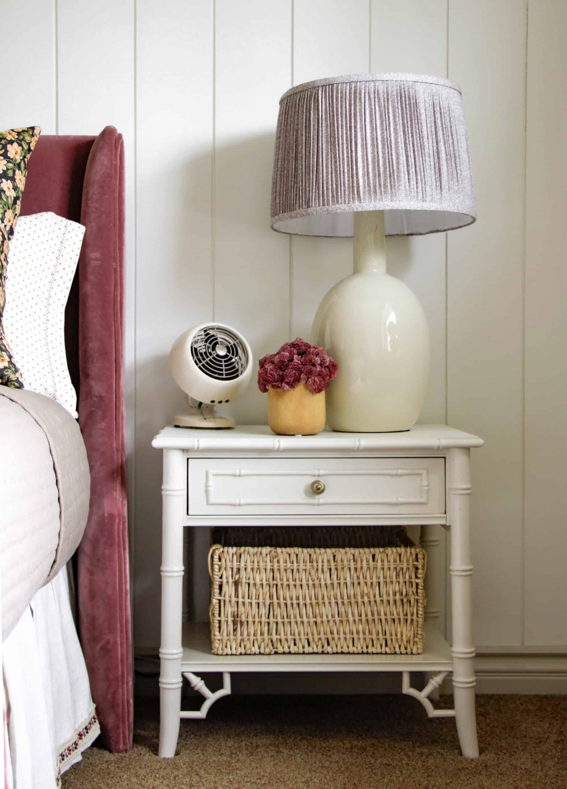 white bamboo nightstand with basket, lamp, fan