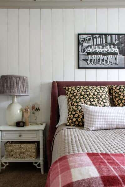 girl's bedroom with pink plaid blanket and black and white photo above bed