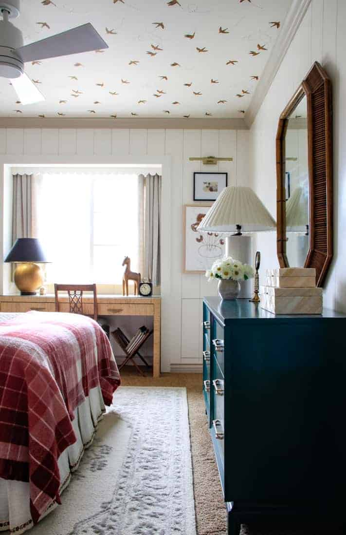girl's bedroom with vertical shiplap and pink plaid blanket