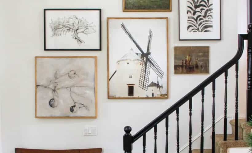 black banister with collected gallery art in staircase