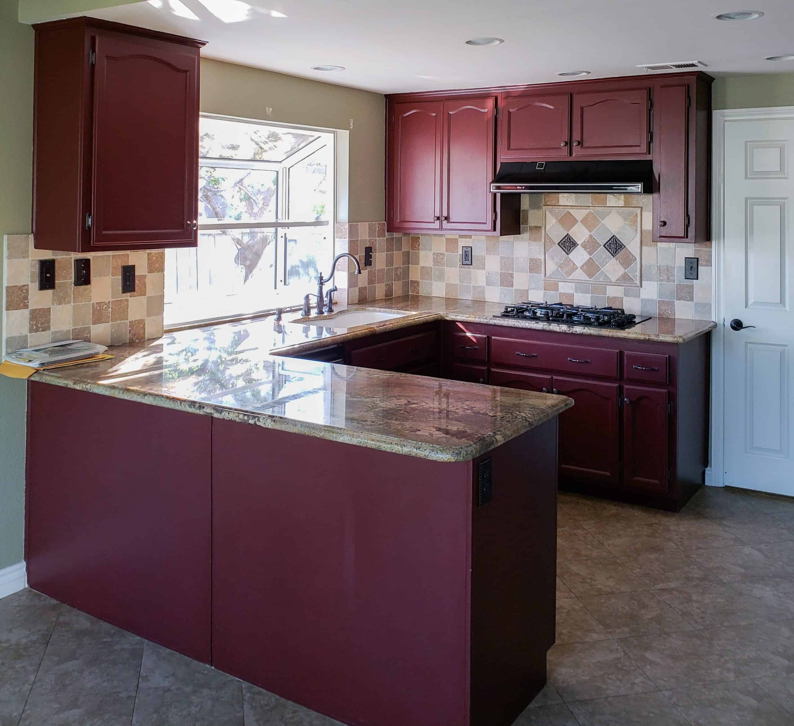 before photo of outdated kitchen with maroon cabinets