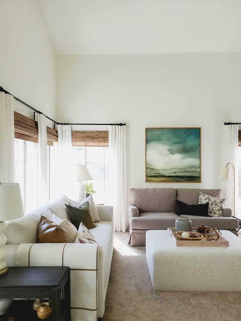 living room with upholstered block ottoman and painting