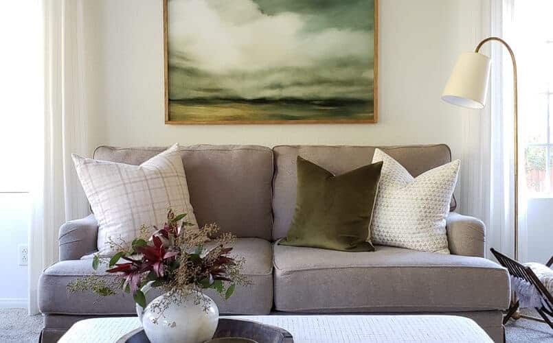 brown sofa with upholstered ottoman and cloud painting