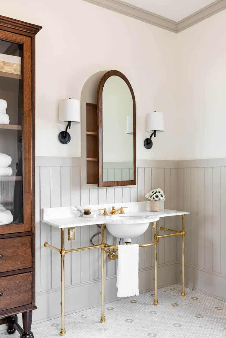 bathroom with arched mirror and tongue and groove wainscoting