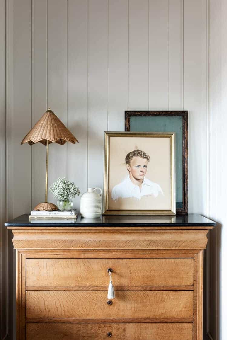 light wood dresser with pictures and rattan lamp on top