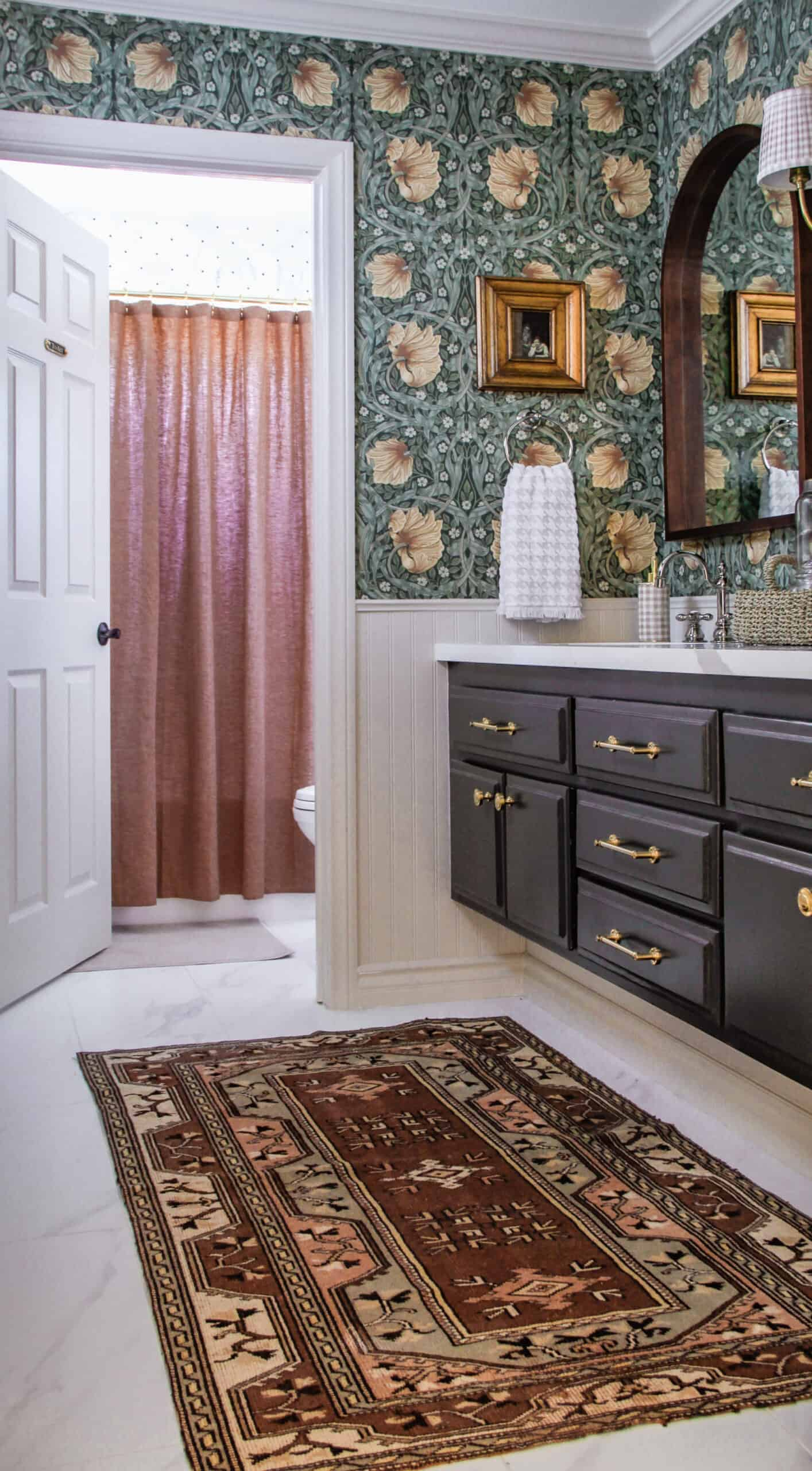 storybook style bathroom with vintage rug and floral wallpaper