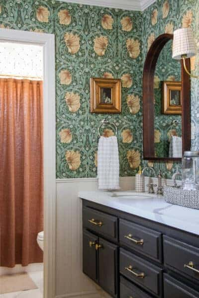 bathroom with floral wallpaper, gold frame, and black vanity