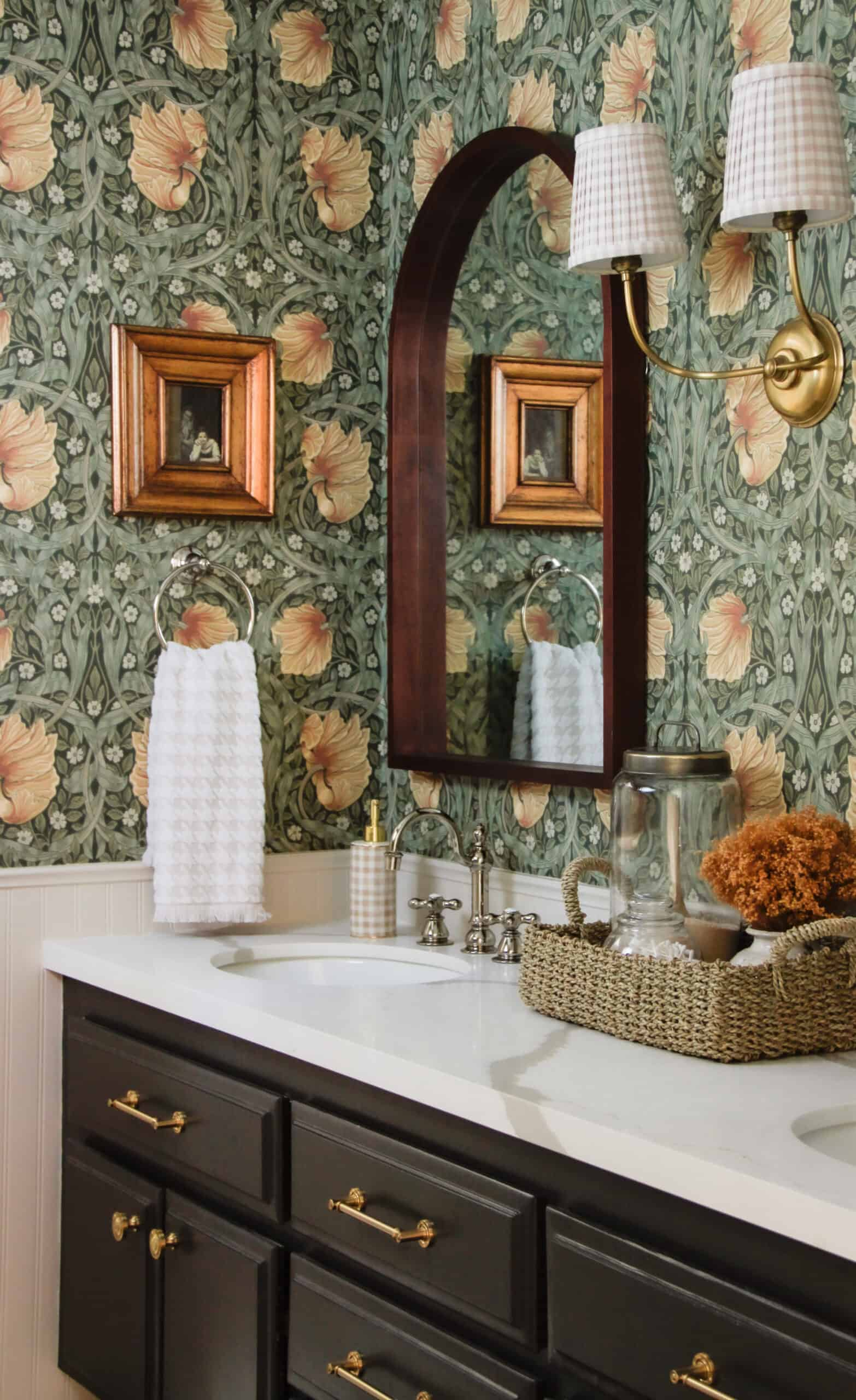 storybook style bathroom with sconce and arched mirror