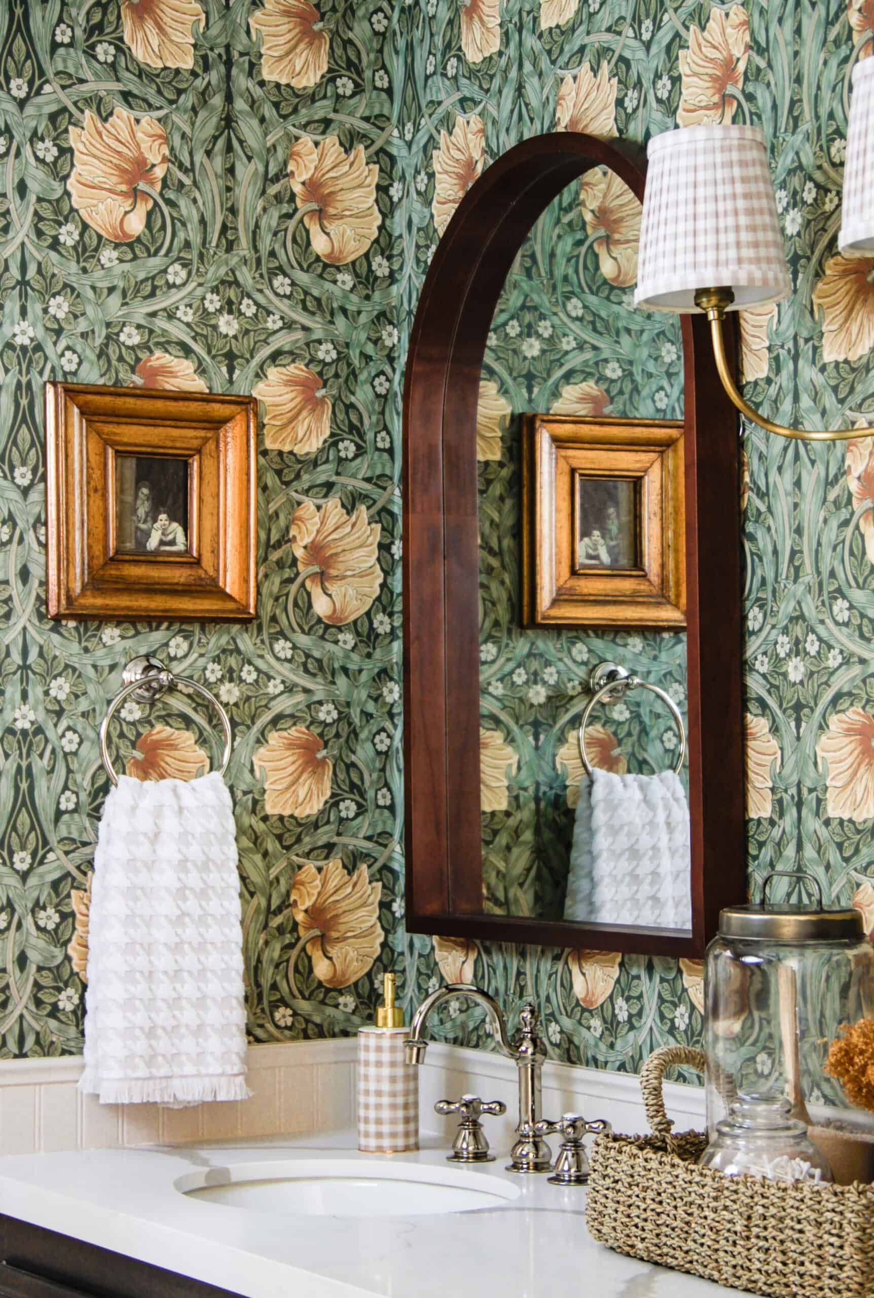 storybook style bathroom with floral wallpaper and arched mirror