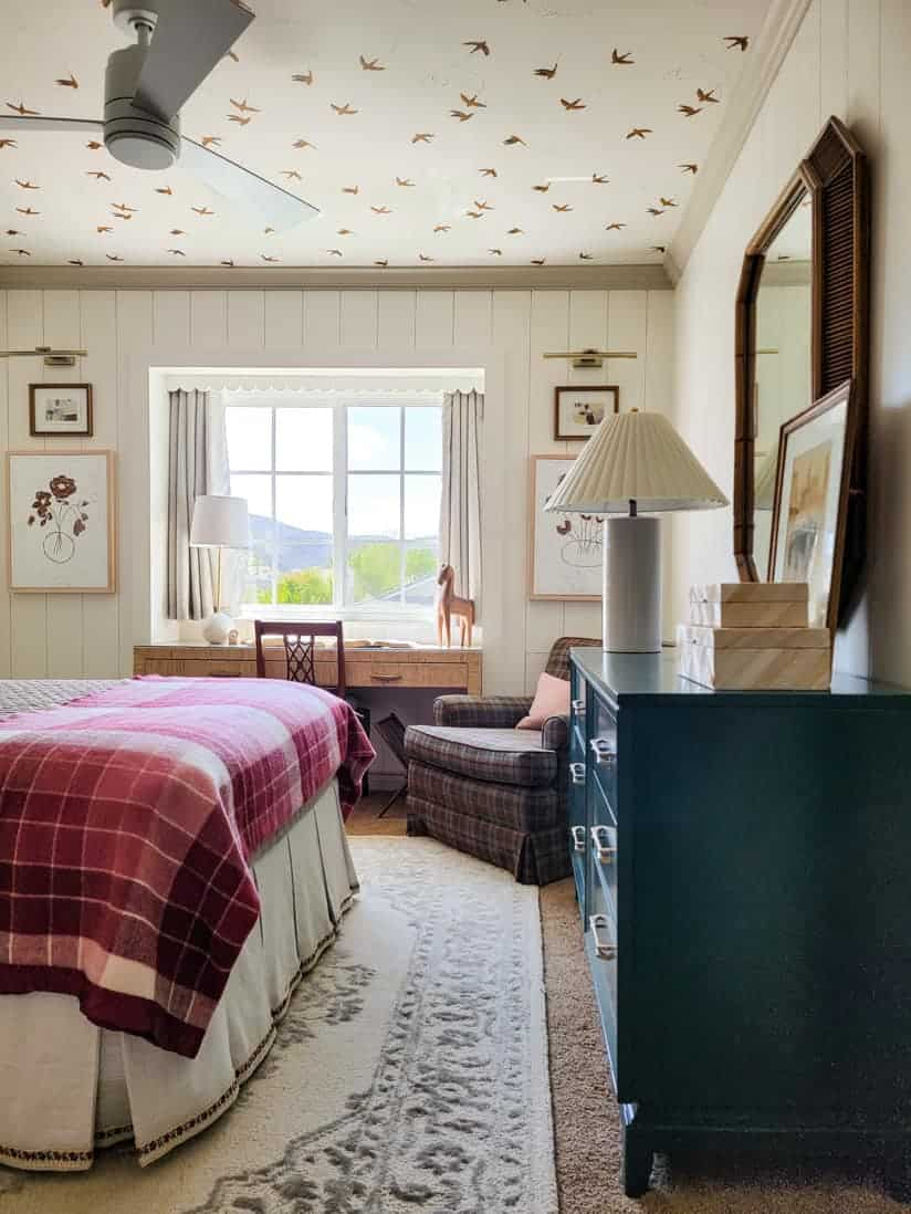 girls' bedroom with pink plaid blanket and bird wallpaper on ceiling
