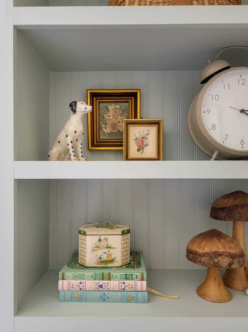 light blue built ins with layered art and a dog figurine