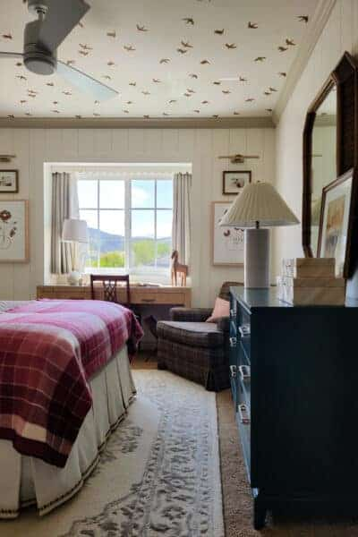 girl's bedroom with pink plaid blanket and bird wallpapered ceiling