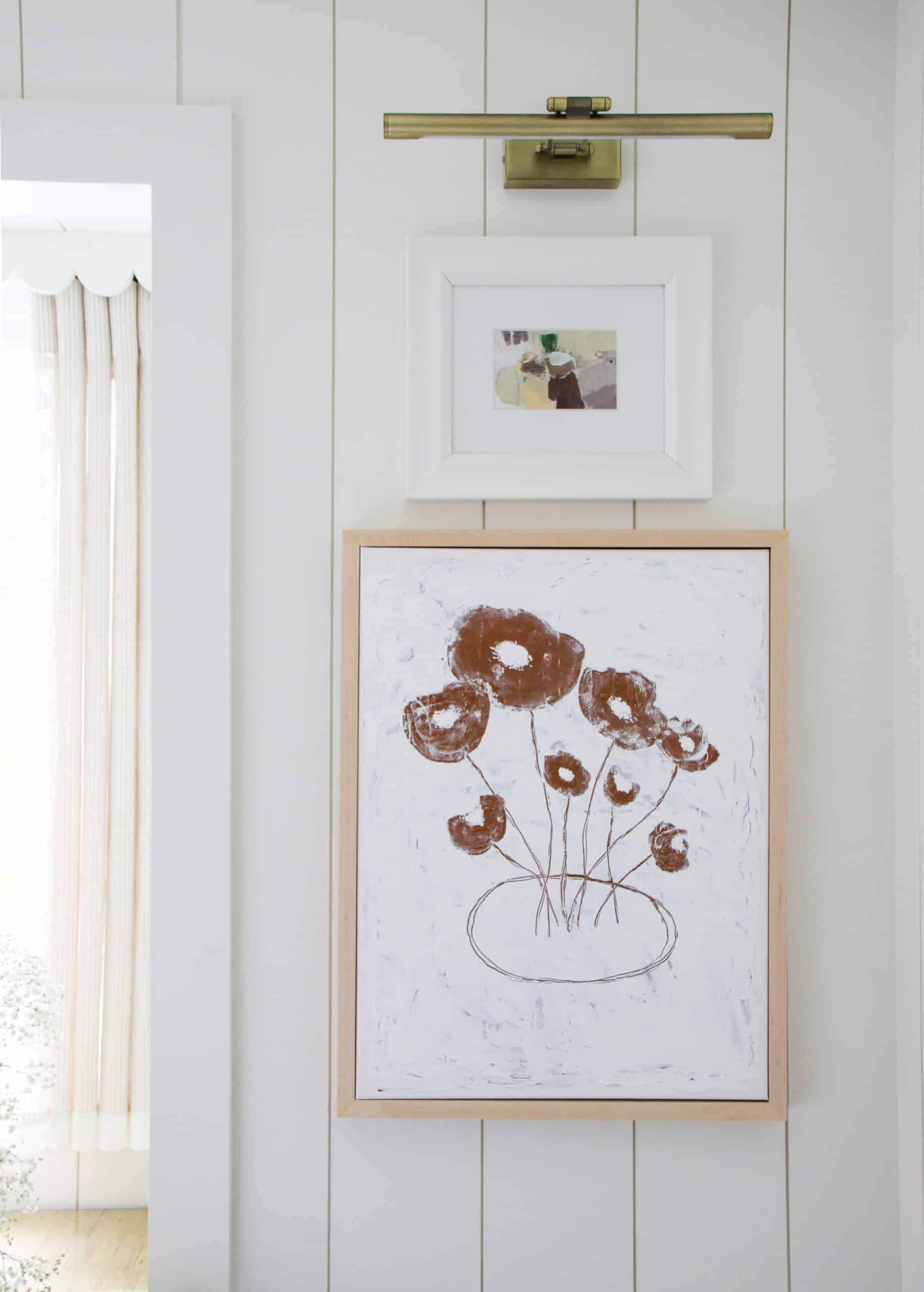 stacked art on white shiplap wall