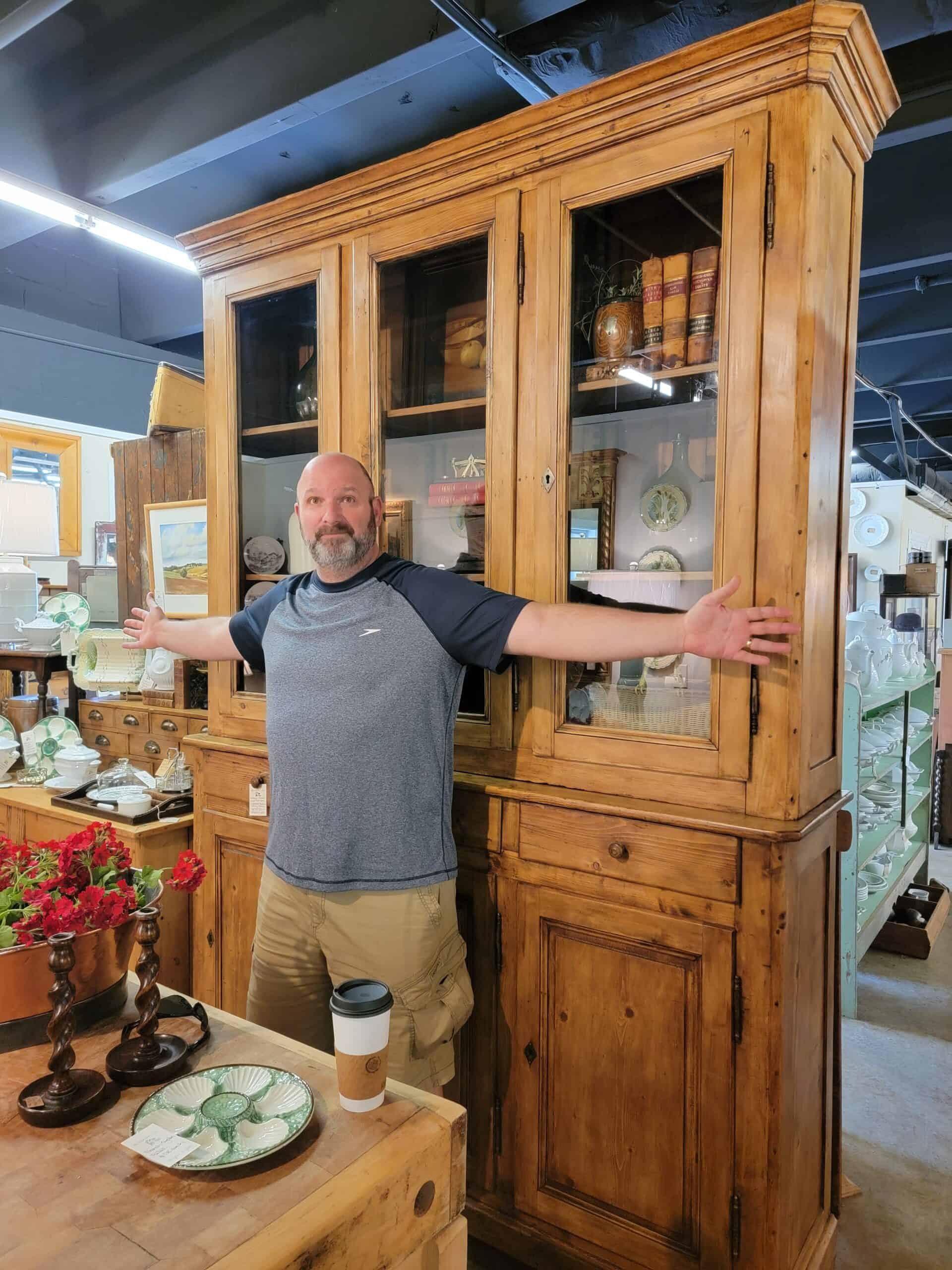 Jeff in front of giant antique cabinet