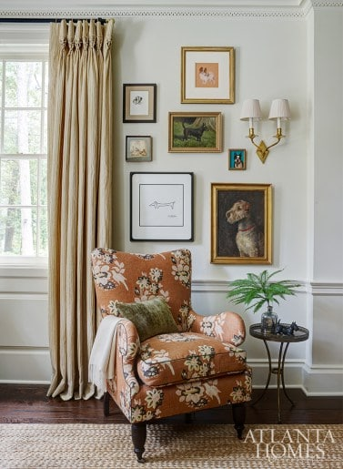 peach floral chair with dog gallery wall above