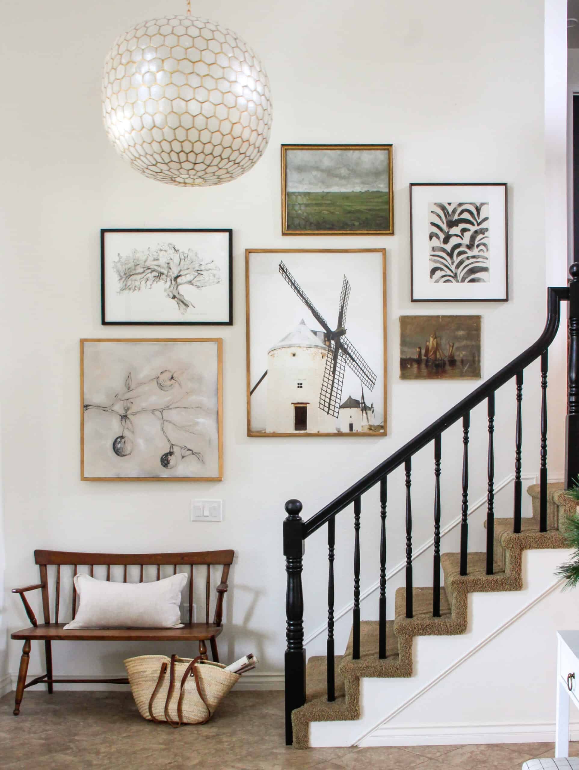 staircase with black banister and gallery wall