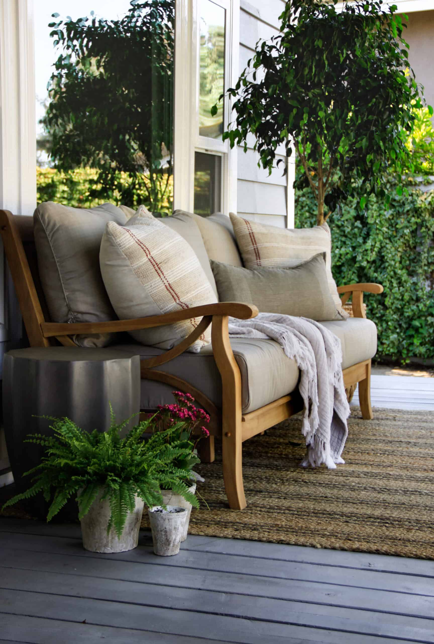 front porch bench on striped jute rug