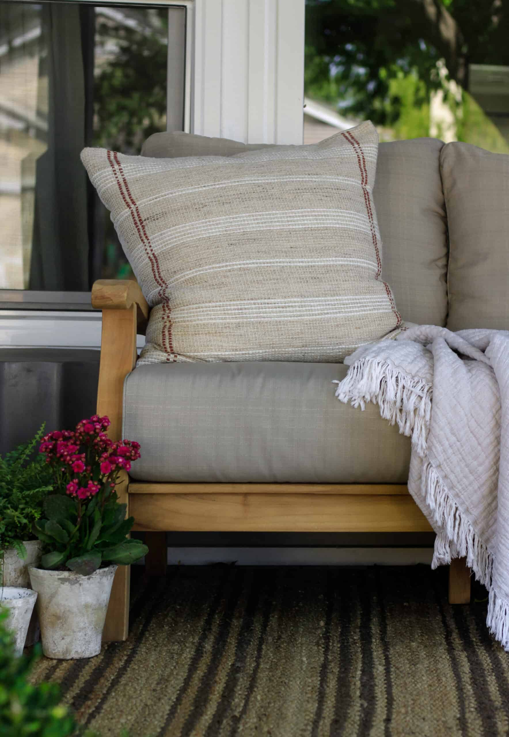 frontal view of porch bench with large pillow and blanket