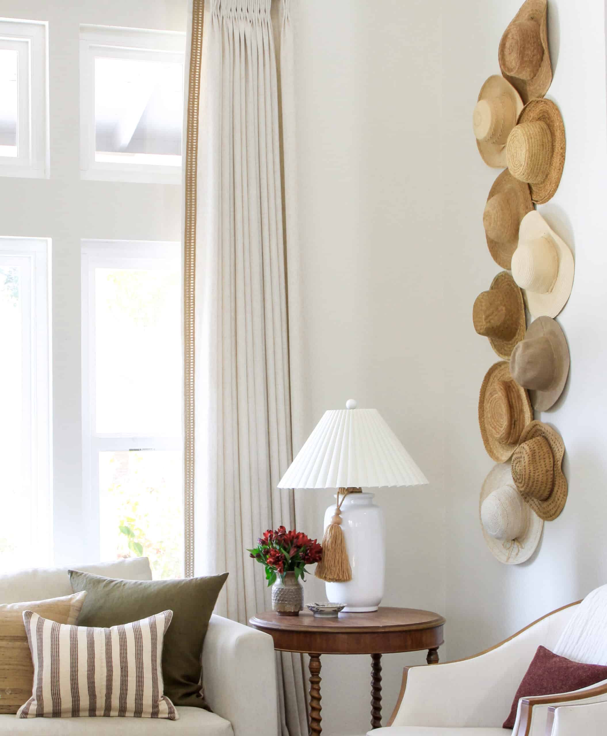 neutral living room with straw hats on the wall, white lamp, and curtains with jute decorative trim