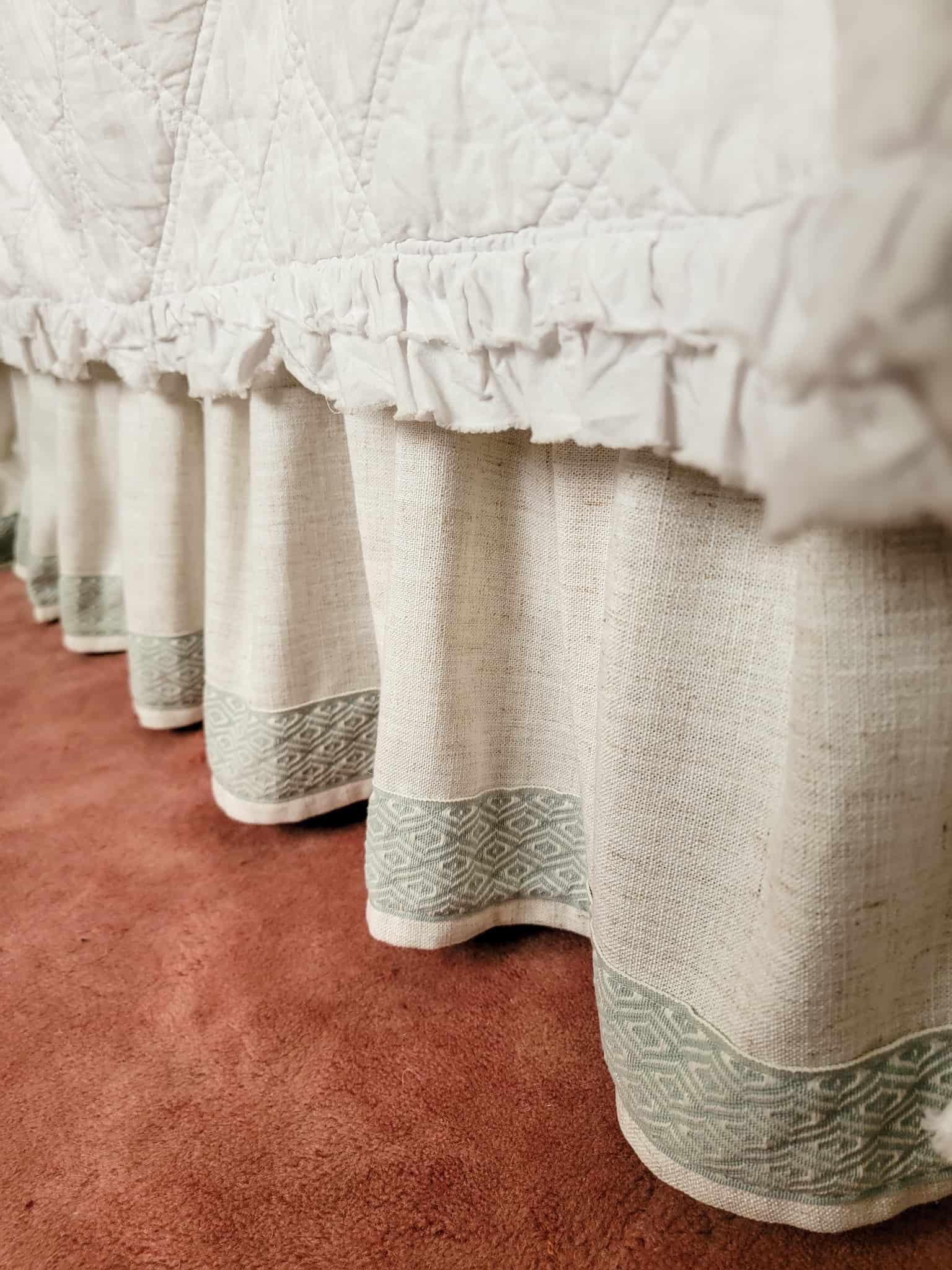 bed skirt with blue decorative trim on top of a pink rug