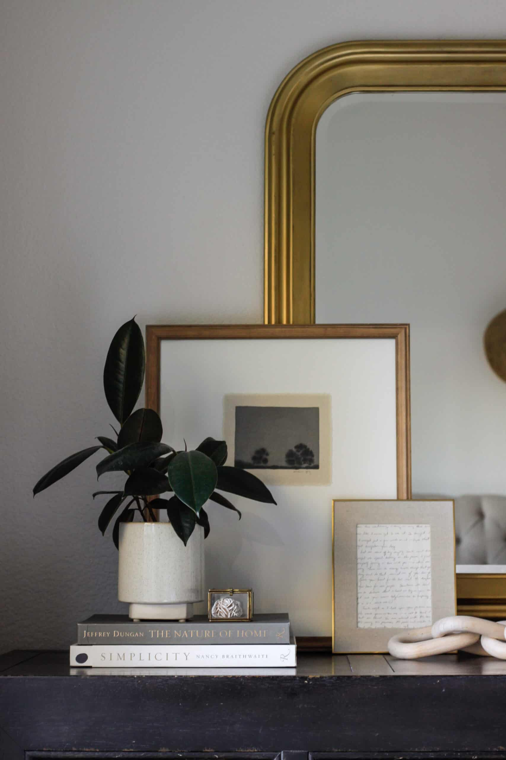 art and a plant layered in front of a gilded mirror dresser decor 3 ways