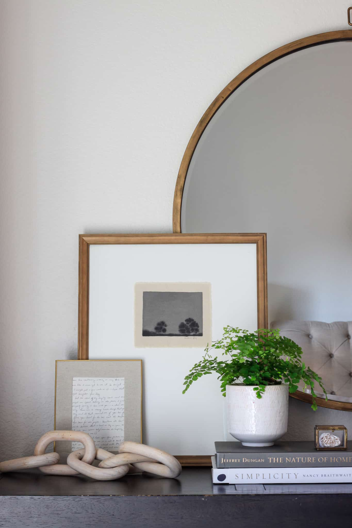 art layered in front of round mirror with plant