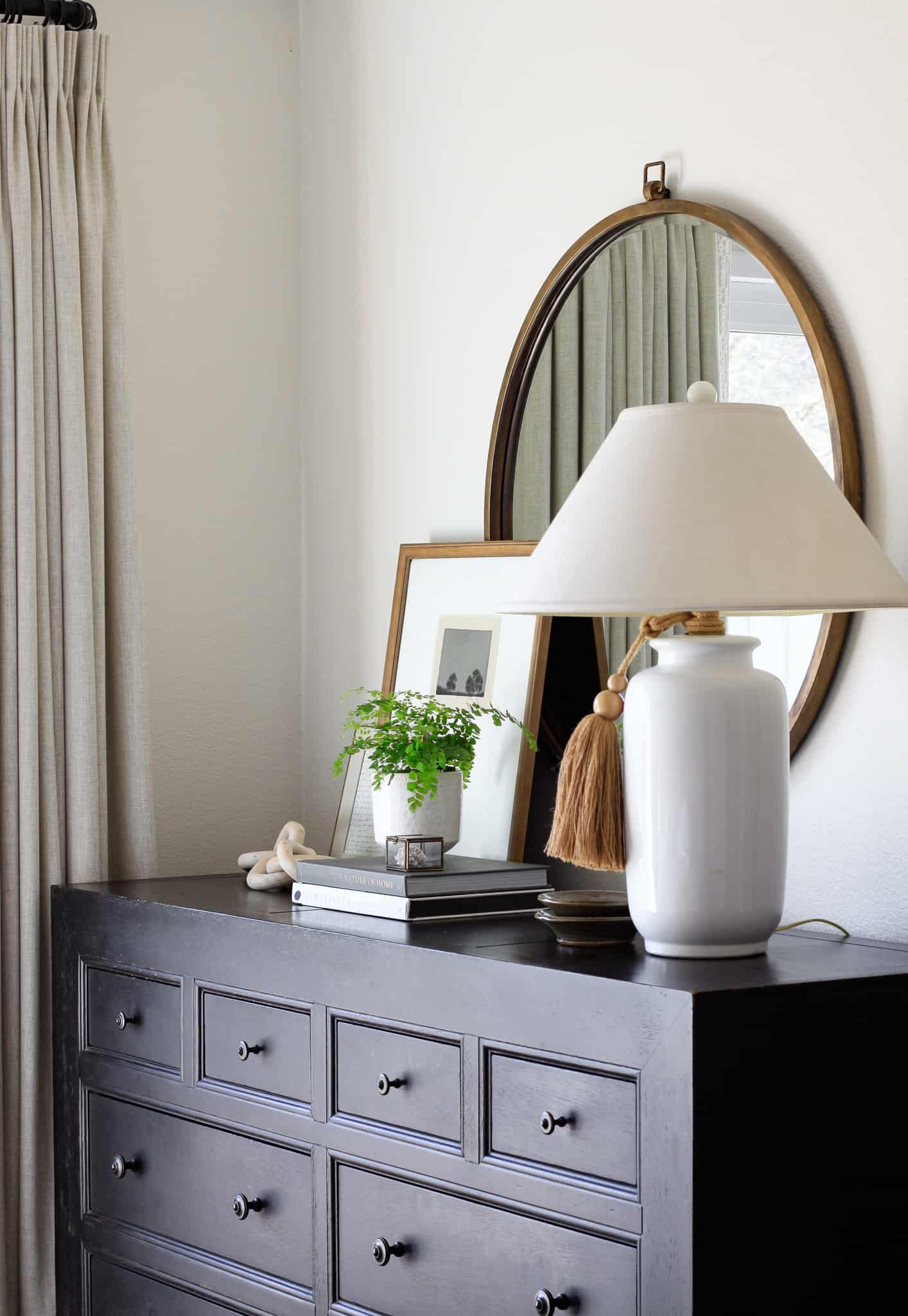 side view of black dresser styled with round mirror, white lamp, and art and plant