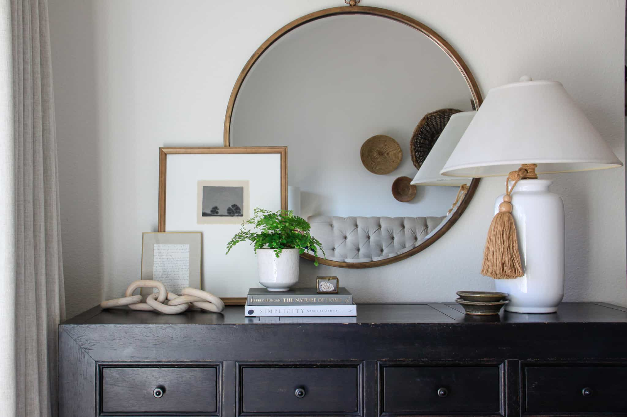 dresser with white lamp, round mirror and art layered in front