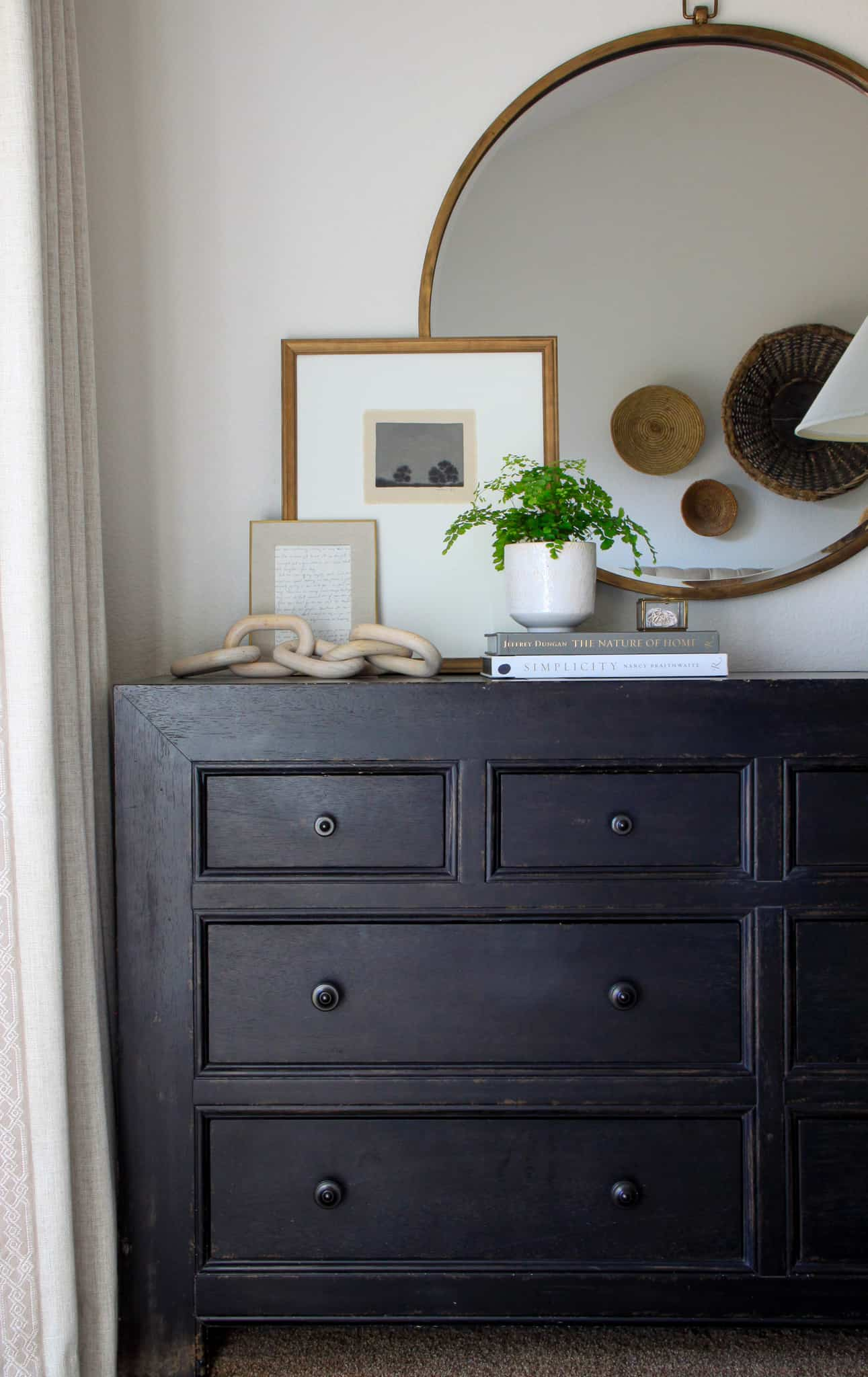 black dresser with round mirror and art layered in front