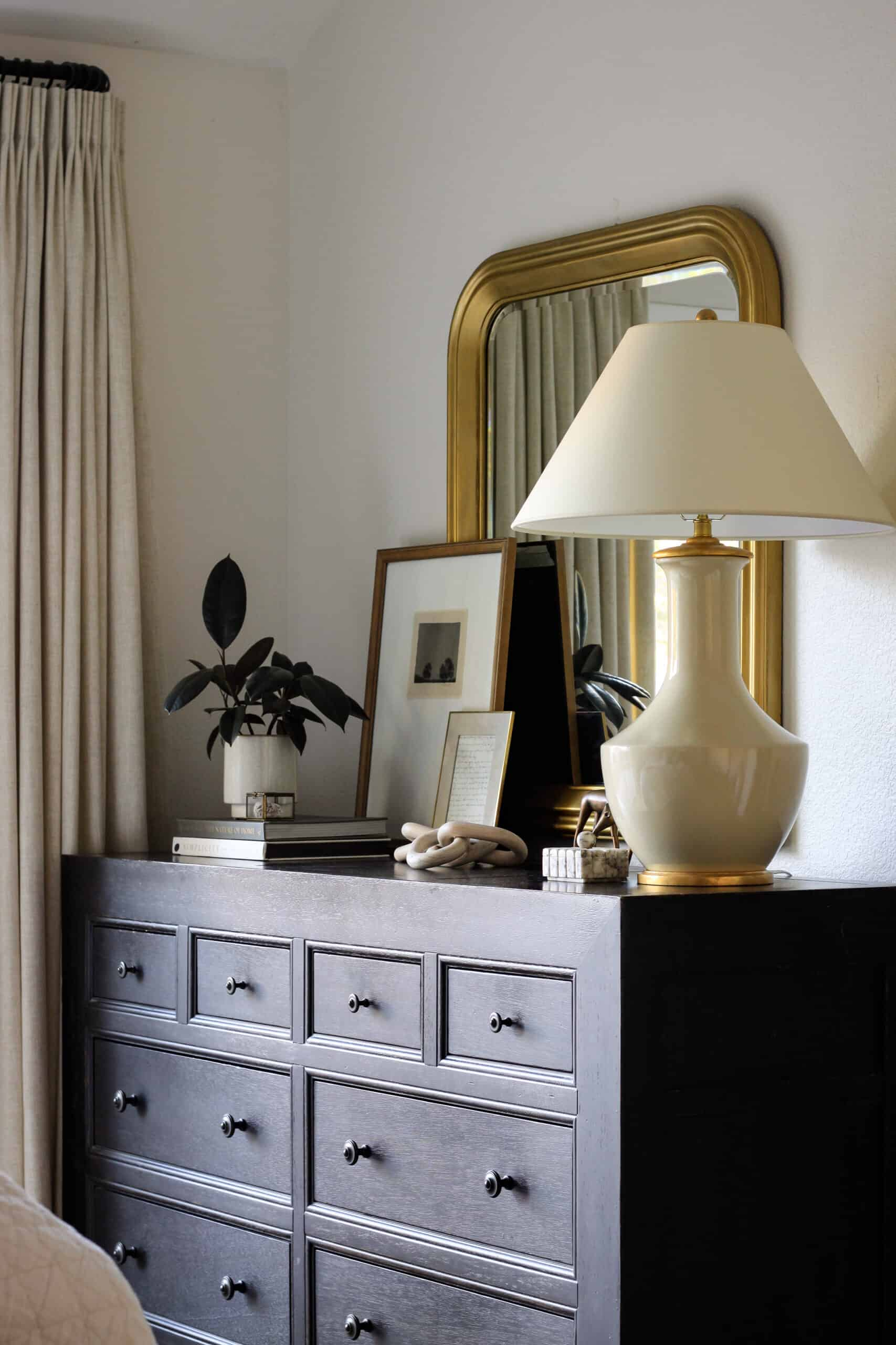 side view of black dresser with cream lamp and gilded mirror with art and a plant