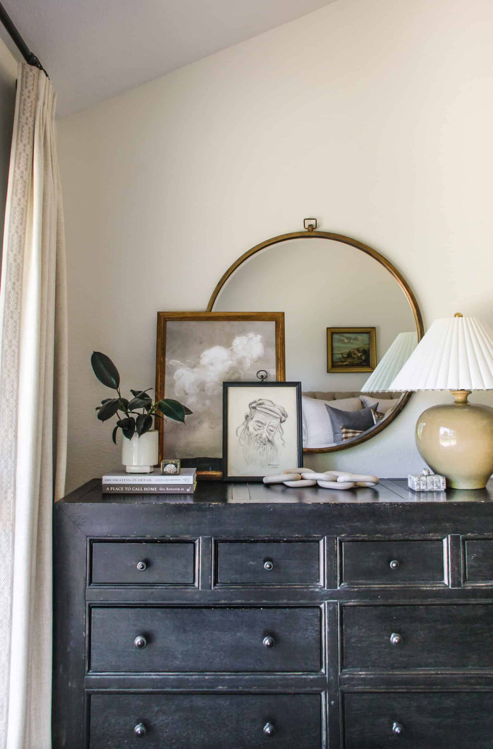 black distressed dresser with round mirror and art stacked in front