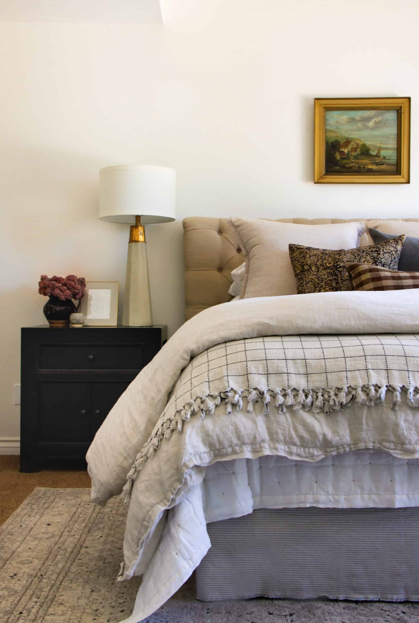 beautiful bed with layered bedding and oil painting above