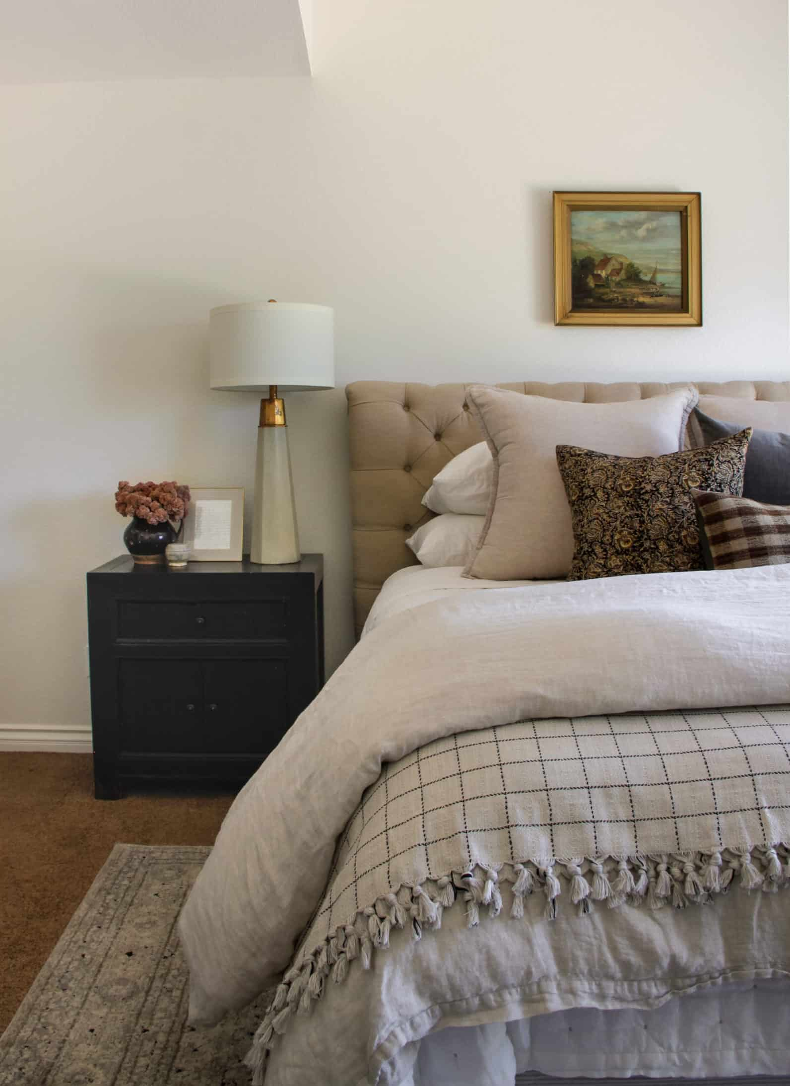 master bedroom bed with black nightstand and oil painting above bed